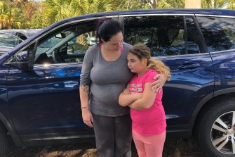 Mandi Parsneau, 34, and her daughter Chloe Ann, 9, wait to return to their home at the Naval Air Station.