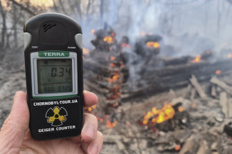 A Geiger counter shows increased radiation level against the background of the forest fire burning near the village of Volodymyrivka in the exclusion zone around the Chernobyl nuclear power plant, Ukraine.
