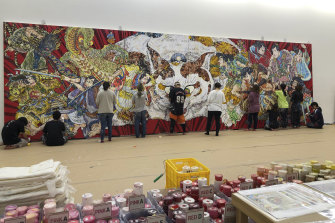 Staff at Takashi Murakami's studio in Saitama, Japan, work on the detailed decorative surface of Murakami's new work for the Art Gallery of NSW.
