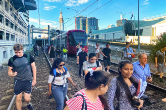 Passengers being evacuated on foot at Exhibition station after a power failure on the light rail, 25 February 2020.