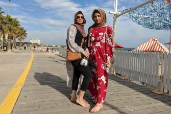 Friends Saba (left) and Iqra meander along the St Kilda boardwalk on Thursday.