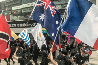 Protesters carry international flags at Causeway Bay in Hong Kong on Sunday.