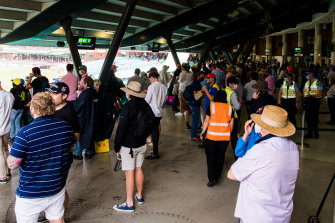 Inside the SCG, people crowd under the stadium to get out of the rain.