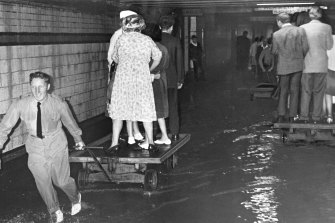 People were pulled along on railway trolleys to get through the flooding in the subway at Flinders Street station.