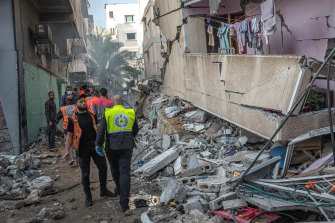 Palestinian civil defence members search for people in the rubble of a destroyed building after an Israeli air strike in Gaza City on May 16.
