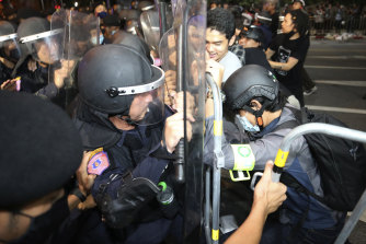 Pro-democracy protesters push Thai police officers with riot shields during a demonstration in Bangkok on Thursday morning. The police dispersed a group of protesters holding an overnight rally outside the Prime Minister's office.