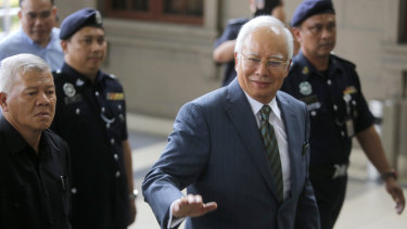 Former Malaysian prime minister Najib Razak, right, arrives at the High Court of Malaya in Kuala Lumpur on Wednesday.