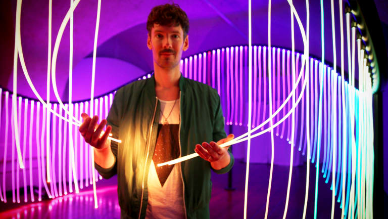 Australian artist Flynn Talbot with his rainbow flag-inspired work at the London Design Biennale.