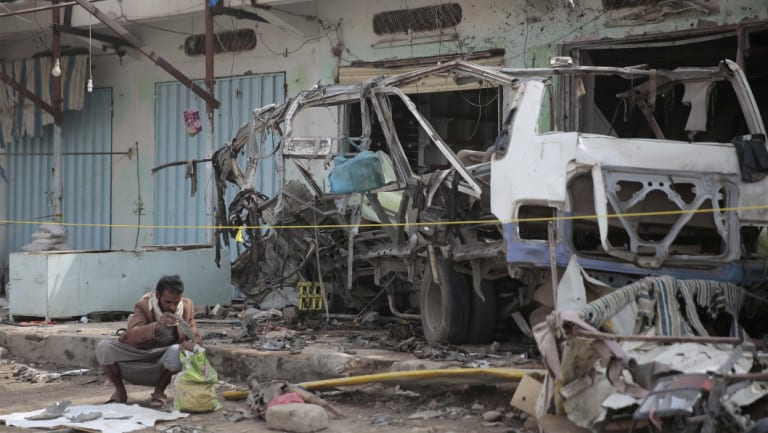A man inspects the wreckage of a bus at the site of a deadly Saudi-led coalition airstrike in Saada, Yemen.