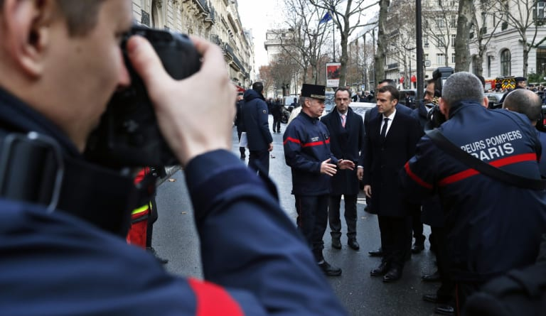 French President Emmanuel Macron meets firefighters and riot police officers on Sunday following violent protests at the Arc de Triomphe.