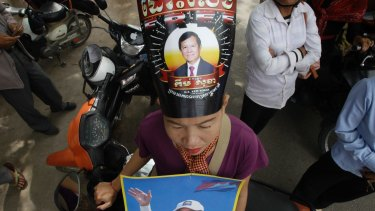 "A supporter of the opposition Cambodia National Rescue Party, wears party president Kem Sokha portrait poster reading""Free"" as she stands outside the Supreme Court in Phnom Penh, Cambodia in October.  Kem Sokha was targeted by a wave of misinformation on social media, before being jailed for alleged 'treason.'"