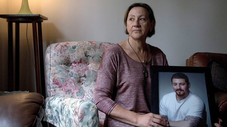 Grace Muscat with a photo of her son Leigh Aiple, who died after cosmetic surgery in Malaysia.