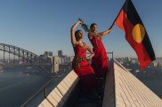 Abigail Delaney and Serene Dharpaloco Yunupingu from the Janawi Dance Clan, from the Darug nation, flying the Aboriginal Flag on top of the Opera House, to promote Dance Rights, a celebration of First Nations Dance.