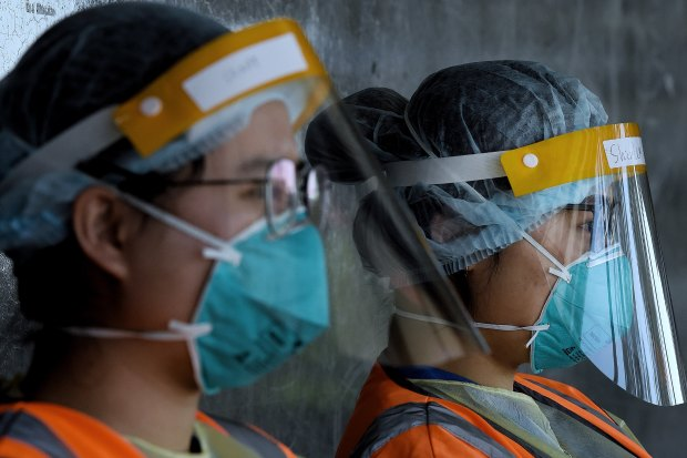 Health workers wearing full PPE wait for people to arrive for testing at a drive-through COVID-19 testing site in Prestons.