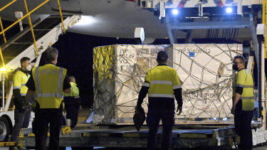 Airport workers unload pallets of the first shipment of the Moderna COVID-19 vaccination as it arrives in Sydney, Australia, Friday, Sept. 17, 2021