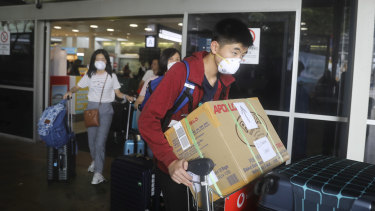 People arriving at Sydney Airport wearing masks.