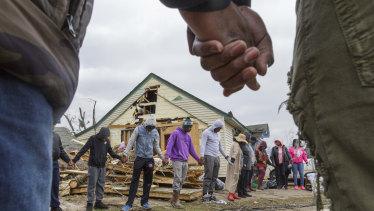Residents of Talibotton, Georgia, pray outside a destroyed home.