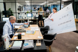Rob Sitch in Utopia comes to grips with decluttering the office ... of giant novelty cheques.