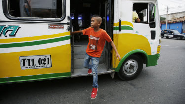 Young Venezuelan migrant Jhon Jader Duno exits a bus after begging for money from commuters in Cucuta, Colombia. Duno said he's trying to raise enough money for he and his mother to move on to another city.