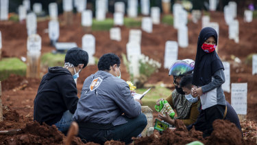 Relatives visit the grave of a COVID-19 victim. The health crisis has forced President Joko Widodo to park his reform agenda.