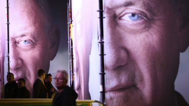 People walk by posters of retired Israeli military chief Benny Gantz before the official launch of his election campaign.