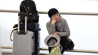A woman waits after Qantas, Jetstar, Tigerair, Rex and Virgin all cancelled multiple flights.