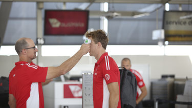 A Swans player having his temperature taken before the team boarded their flight to Adelaide on Friday.