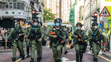 Riot police in Hong Kong head toward an anti-government protest on September 6.