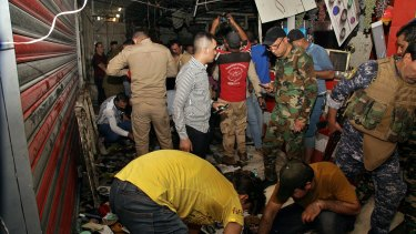 People and security forces gather at the site of a bombing at a market in Sadr City, Iraq.