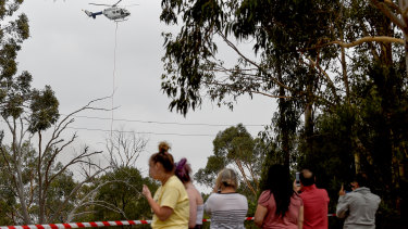 Residents watch on as a water bomber helicopter is seen as a fire burns out of control near Voyager Point, Sydney