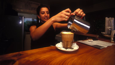 A barista displaying for skill at a Brisbane cafe.