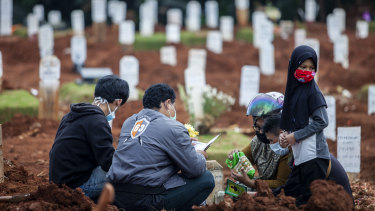 Relatives visit the grave of a COVID-19 victim.
