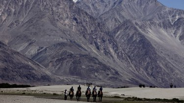 Tourists ride double hump camels at Nubra valley, in Ladakh, India - the scene of a stand-off between nuclear powers India and China.