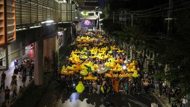 Protesters march while carrying inflatable yellow ducks outside the headquarters of army regiment in Bangkok, Thailand.
