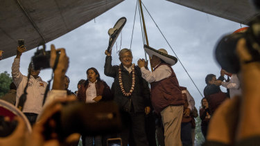 Andrés Manuel López Obrador, a presidential candidate commonly known as AMLO, greets the crowd during a campaign rally in Chimalhuacán, on the outskirts of Mexico City.