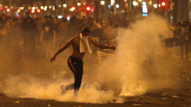 A man kicks a tear gas canister thrown by riot police during clashes on the Champs Champs Elysees avenue where soccer fans were celebrating France's World Cup victory.