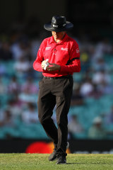 Australian umpire Sam Nogajski cleans the ball after it was returned from the crowd from a six during game one of the One Day International series between Australia and India at Sydney Cricket Ground.