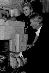 'Mr an Mrs Lindley Evans of Werambie Street, Woolwich place wood into the fireplace before leaving for a concert. On returning they light the fire and then listen to the Test Match.'