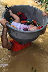 A baby is rescued from a flooded village in the Cagayan valley, northern Philippines on Friday.