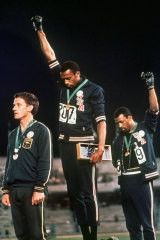 """American athletes Tommie Smith, centre, and John Carlos extended gloved hands in a protest at the Mexico City Games in 1968. Silver medallist Australia's Peter Norman stands on the left. He wore a badge supporting the """"Olympic Project for Human Rights""""."""
