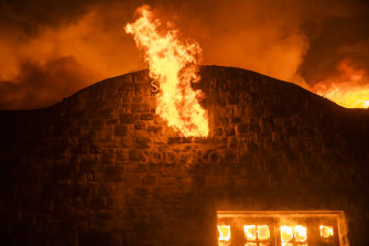 Flames escape from the broken window of a burning building at the Soda Rock Vineyards during the Kincade fire in Healdsburg, California.