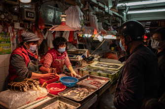 Residents wearing face mask buy seafood at a wet market in China.