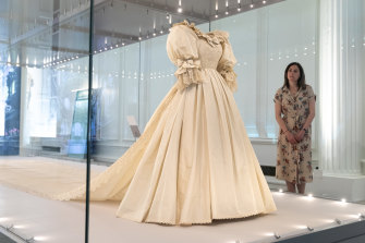 """A visitor views Diana, Princess of Wales's wedding dress displayed complete with its spectacular sequin encrusted train at the """"Royal Style In The Making"""" exhibition at Kensington Palace."""