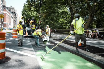 Workers prepare a new protected bike lane along Central Park West in Manhattan, near where Australian Madison Jane Lyden was killed on a bike.