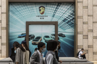 People walking in front of a yet to be opened showroom for China Evergrande New Energy Vehicle Group's electric vehicles in Shanghai in mid-September.