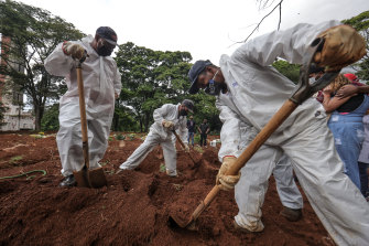 Workers wearing protective gear bury the casket of a COVID-19 victim  in Sao Paulo, Brazil, on Friday. The country has lost more than 200,000 people to the new coronavirus.