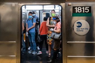 Commuters wearing masks board the subway during morning rush hour in New York.