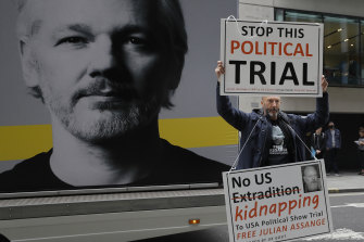 A demonstrator holds placards in support of Julian Assange near the Old Bailey in London this week.
