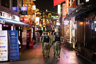 US Army military police patrol the street at night in the Itaewon area of Seoul, South Korea.