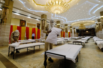 Civil defence members prepare beds in a makeshift quarantine ward in the OraBella Banquet hall in New Delhi.